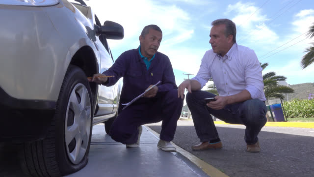 Adult male talking to a mechanic to fix the tire