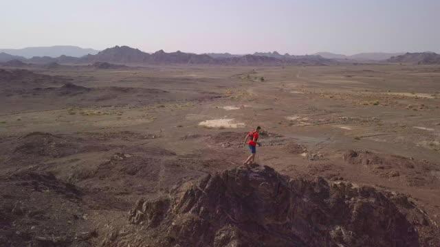 erwachsene männliche trailrunning über bergige wüstenlandschaft - oman stock-videos und b-roll-filmmaterial