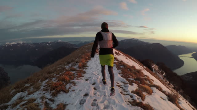 adult male trail runs on snowy mountain ridge above lake at sunset - top capo di vestiario video stock e b–roll