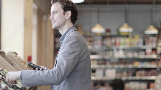 vídeos y material grabado en eventos de stock de adult male using self scan in a grocery store - super slow motion