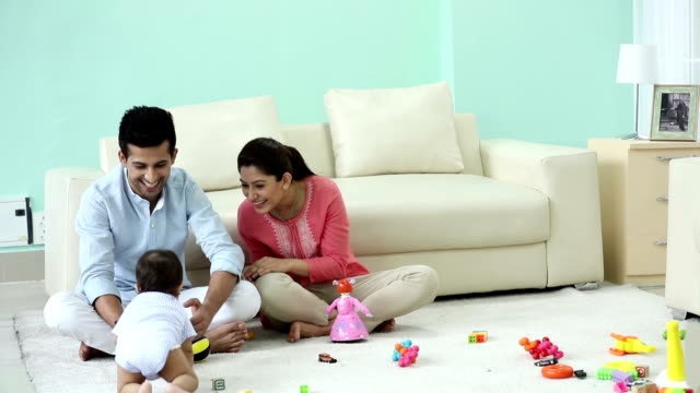 adult man and adult woman playing with their baby at home, delhi, india - 床に座る点の映像素材/bロール