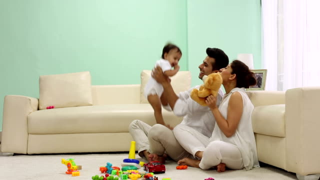 Adult man and adult woman playing with their baby at home, Delhi, India