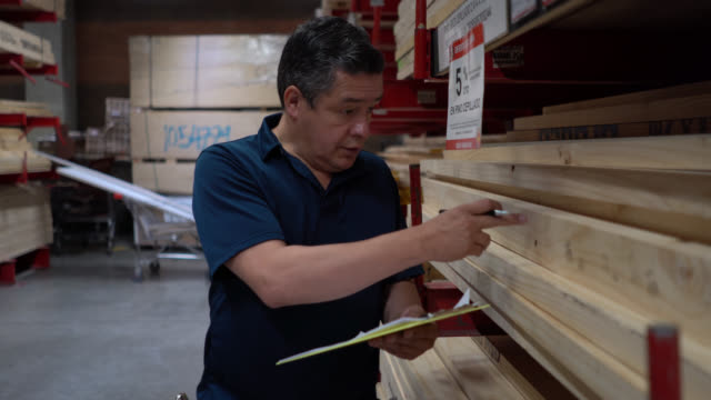 adult man at a wood warehouse doing inventory counting and writing down everything using a clipboard and pen - construction material stock videos & royalty-free footage