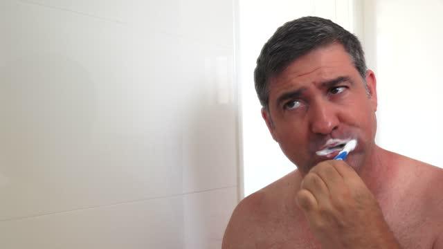 adult man brushing teeth with toothbrush - 歯みがき点の映像素材/bロール