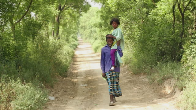 Adult man carrying her daughter on his shoulder, Haryana, India
