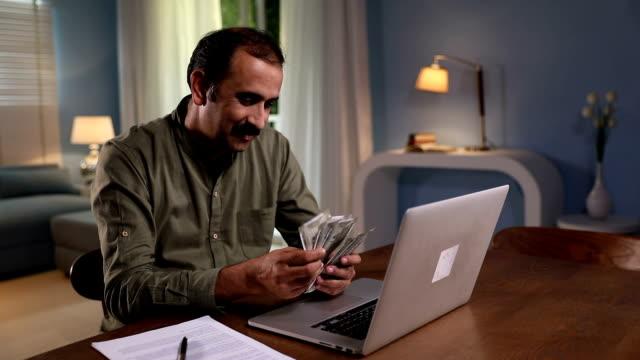Adult man counting indian banknotes, Delhi, India