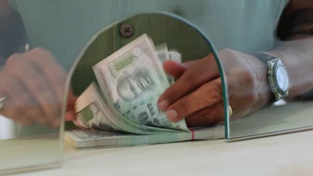 Adult man counting money at bank counter, Delhi, India