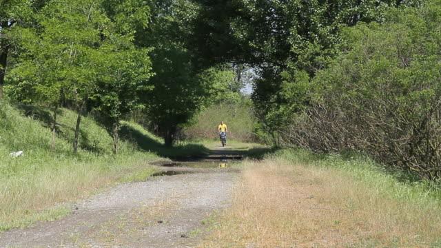 Adulte homme Cyclisme sur route de campagne avec les flaques