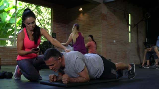 Adult man doing a plank and personal coach timing him while correcting posture