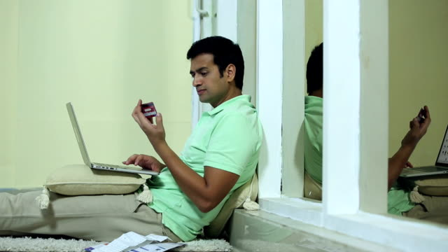 adult man doing online shopping on laptop, delhi, india - home finances stock videos & royalty-free footage