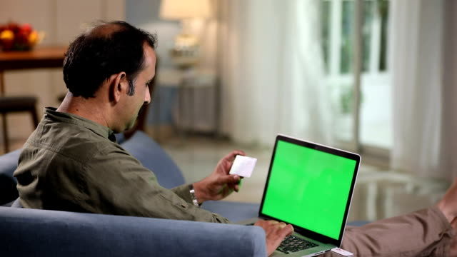 Adult man doing online shopping on laptop, Delhi, India