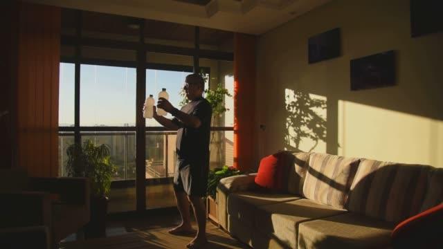 vídeos de stock, filmes e b-roll de homem adulto fazendo exercício físico em casa - interior de casa