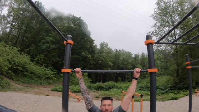 Adult Man Doing Pull Ups Outdoors in Rain