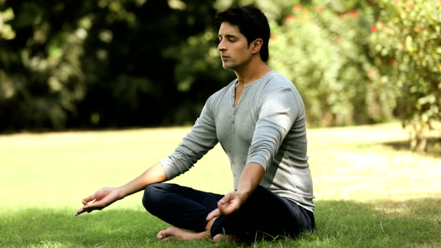 Adult man doing yoga in the park, Delhi, India