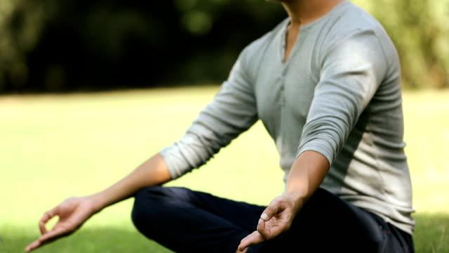 vidéos et rushes de adult man doing yoga in the park, delhi, india - assis en tailleur