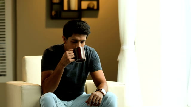 Adult man drinking tea in the home, Delhi, India