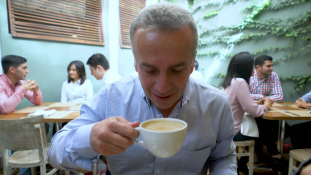 Adult man enjoying a coffee and talking to someone looking happy