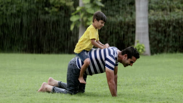 vídeos de stock e filmes b-roll de adult man enjoying in the rain with his son, delhi, india - família monoparental