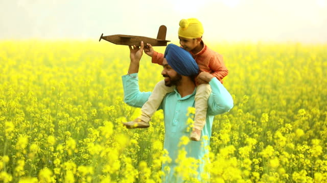 Adult man enjoying with his son in the mustard farm, Punjab, India