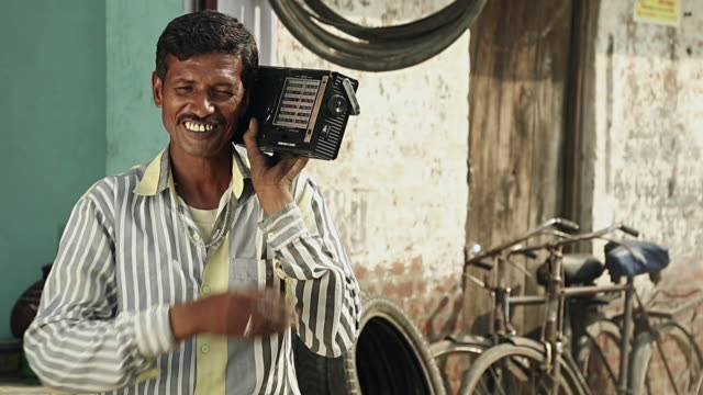 Adult man hearing music on radio, Haryana, India