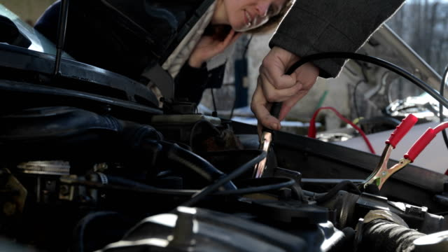 adult man helping a woman to jump start a car - a helping hand stock videos & royalty-free footage