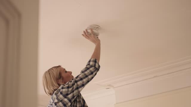 adult man installing smoke alarm in home - installare video stock e b–roll