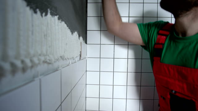 adult man installing tiles on the wall - bathroom stock videos & royalty-free footage