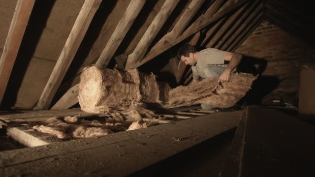 adult man insulating attic with insulation material - isoliermaterial stock-videos und b-roll-filmmaterial