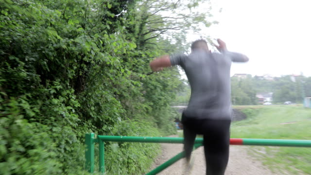 vídeos y material grabado en eventos de stock de hombre adulto saltando sobre una barrera en country road - valla límite