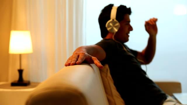 Adult man listening music on headphone, Delhi, India