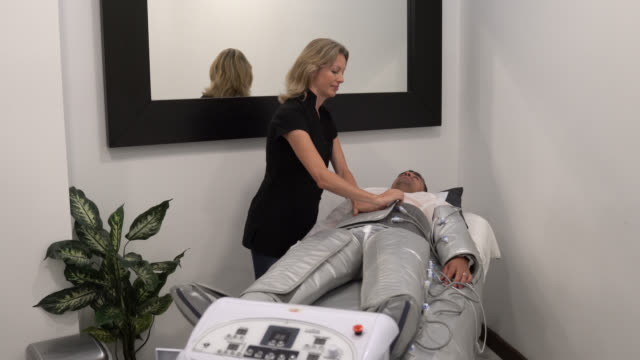 adult man lying down while beautician is preparing him for a pressotherapy at the spa - pressotherapy stock videos and b-roll footage