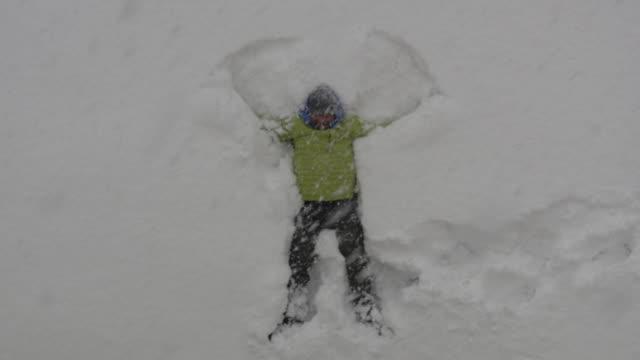 adult man lying in fresh snow, making snow angels having fun - human limb stock videos & royalty-free footage