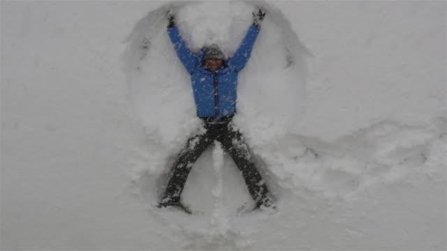 Adult man lying in fresh snow, making snow angels having fun