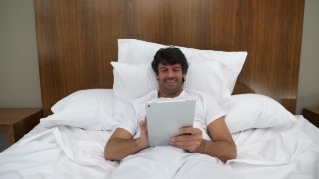 Adult man lying on his bed at home chatting using a digital tablet looking very happy and laughing
