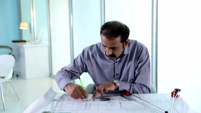 Adult man making drawing of building in the office, Delhi, India