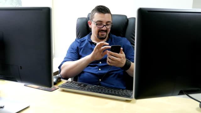 Erwachsener Mann Büroleiter und Arbeiter mit seinen Smartphone am Arbeitsplatz