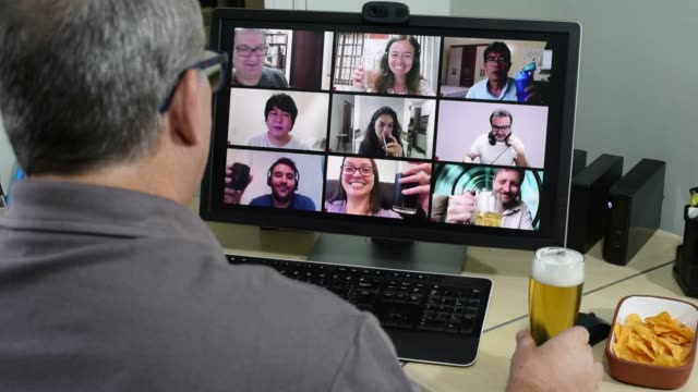 adult man on conference call with friends doing happy hour - virtual event stock videos & royalty-free footage