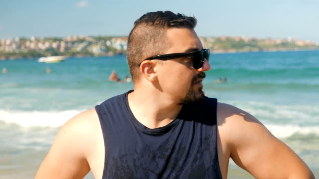 vídeos y material grabado en eventos de stock de hombre adulto en la playa mirando a cámara - vigilante