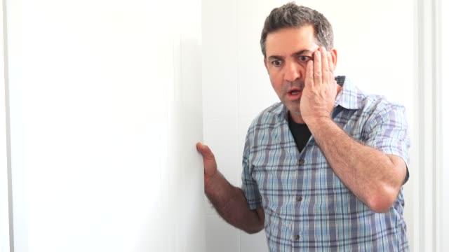 vídeos de stock e filmes b-roll de adult man opens a door shocked from what he sees - medo