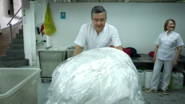 adult man pushing a basket full of sheets ready to load them into washing machine at a laundry service - lavanderia pubblica video stock e b–roll