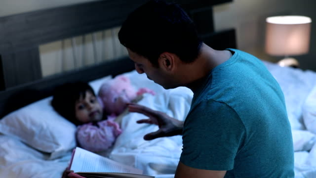 adult man reading storytelling book with his daughter, delhi, india - ora di andare a letto video stock e b–roll
