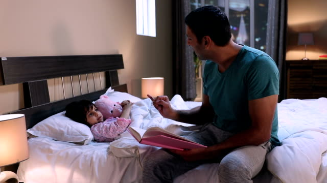 adult man reading storytelling book with his daughter, delhi, india - erzählen stock-videos und b-roll-filmmaterial