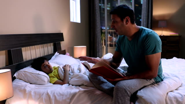adult man reading storytelling book with his son, delhi, india - bedtime stock videos & royalty-free footage