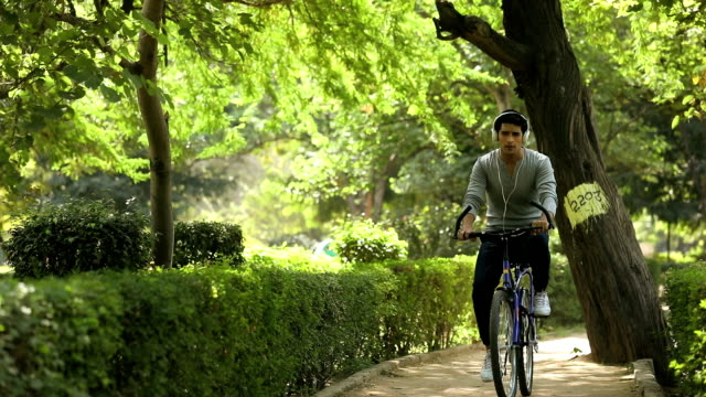 stockvideo's en b-roll-footage met adult man riding bicycle in the park, delhi, india - hoofdtelefoon