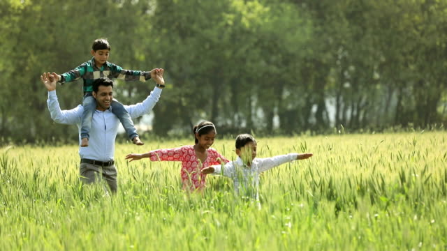 vídeos y material grabado en eventos de stock de adult man running with kids in the farm, haryana, india - haryana