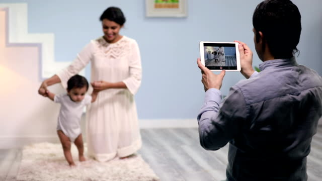 adult man shooting video of his family with a digital tablet, delhi, india - erste schritte stock-videos und b-roll-filmmaterial