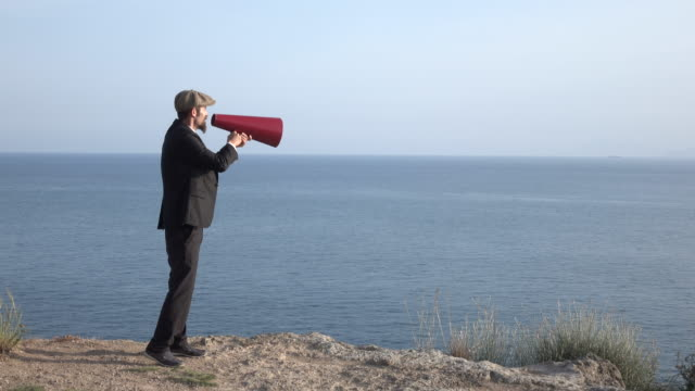 adult man shouting via old fashioned megaphone in outdoor - megaphone stock videos & royalty-free footage