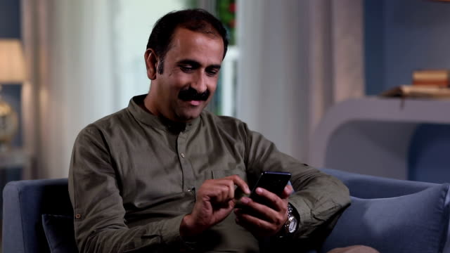 adult man showing mobile phone at home, delhi, india - moustache stock videos and b-roll footage