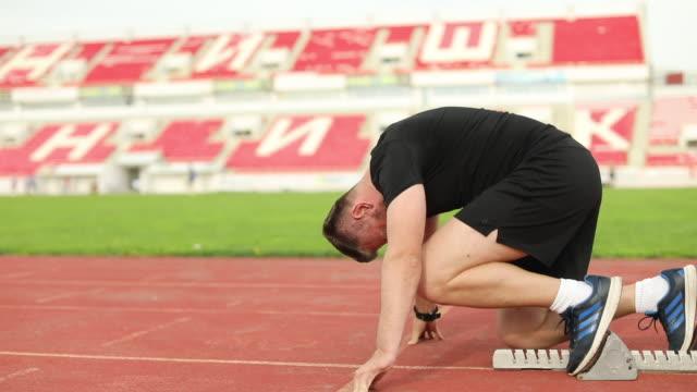 100 m ダッシュを開始の成人男性 - スターティングブロック点の映像素材/bロール