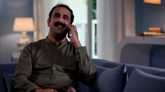 Adult man talking on mobile phone at home, Delhi, India